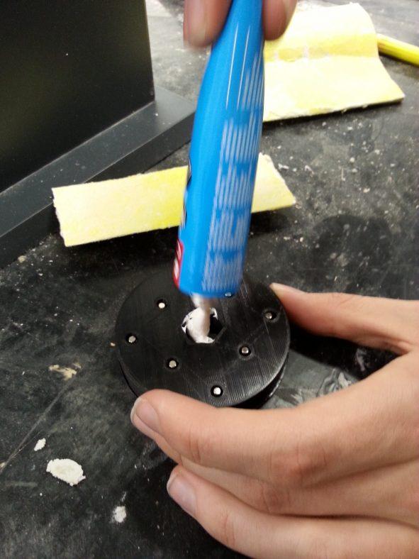 Lukon hattu juuri ennen liimaamista kiinni akseliin, magneetit ovat myös paikoillaan hatun rei'issä. Tässä kuvassa käytetään liimatiivistemassaa, joka ei toiminut hyvin. Lopullisessa protossa tehtiin sama juttu käyttäen kuumaliimaa, mutta siitä ei ole kuvaa.