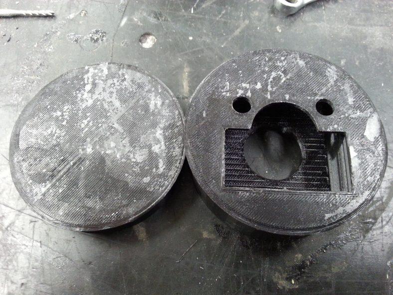 Lukon 3D-printatut osat toiselta puolelta, vasemmalla lukon hattu ja oikealla kiinteä osa