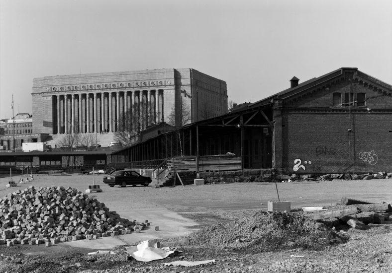 Töölön tavara-asemaa vuonna 1999 ennen tulipaloa. Makasiinien välistä piha-aluetta, taustalla Eduskuntatalo. HKM, Kari Hakli. https://www.helsinkikuvia.fi/record/hkm.HKMS000005:km002iak/